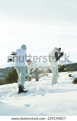 Young friends throwing snowballs at each other, full length - stock photo