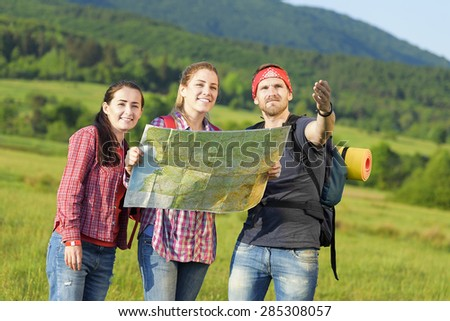 Young friends tourists with map in the park. Adventure. - stock photo