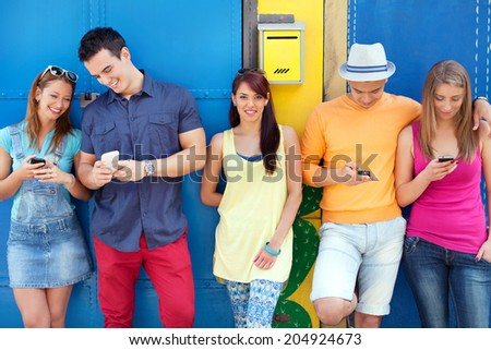 Young friends using mobile phones while hanging out - stock photo