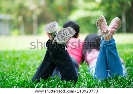 Young friends wearing sneakers lying on the grass in summer - stock photo