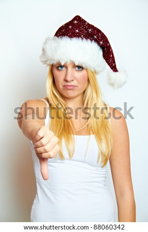 young frustrated christmas woman with thumb down - stock photo