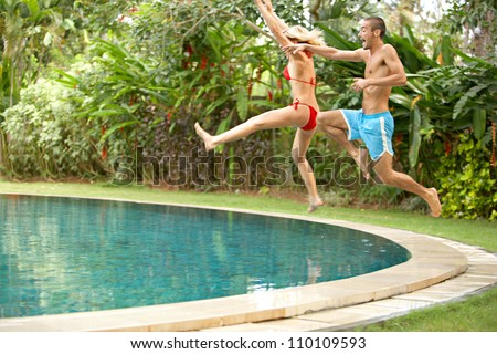 Young fun couple jumping into a tropical swimming pool while on vacations in a tropical destination. - stock photo