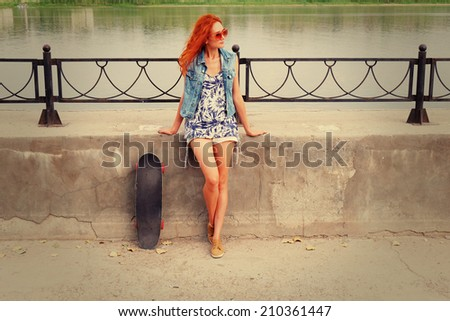 Young funky woman is posing with a skateboard leaning back against embankment fence. Redhair teen in short jeans shorts standing alone in warm day with her longboard urban hipster trendy outdoor photo - stock photo
