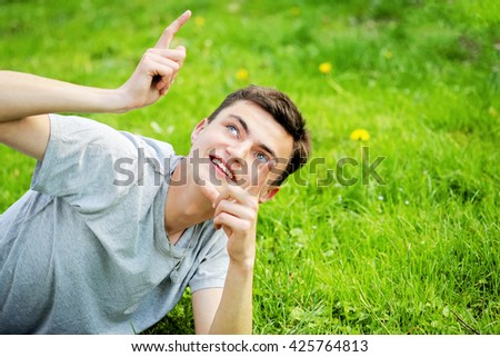 Young funny blue-eyed handsome dark-haired man in gray t-shirt and jeans on the green lawn in green sunny spring park. Happy smiling boy resting on the grass. - stock photo
