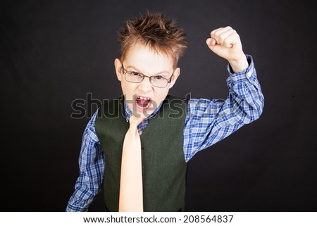 Young funny boy grimacing over the black - stock photo
