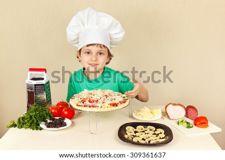 Young funny boy in chefs hat shows how to cook a pizza - stock photo
