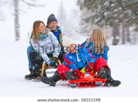 young funny family is sledging in winter-landscape - stock photo