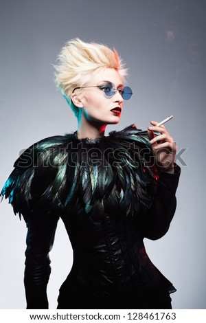 young futuristic woman with punk style hair and eye glasses holding a cigarette and posing on blue background - stock photo