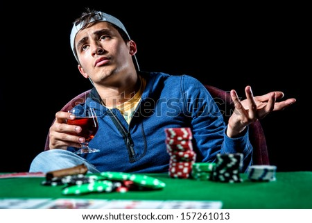 Young gambler holding glass of cognac  - stock photo