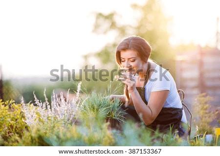 Young gardener in garden smelling flower, sunny nature - stock photo