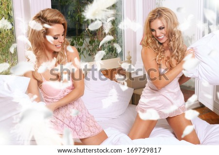 Young gay couple fighting pillows in the bedroom  - stock photo
