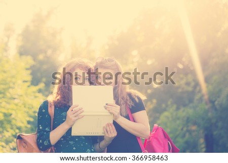 Young gay girlfriends in a city park. Girl hiding behind a laptop screen. Social networking. Best friends. BFF - stock photo