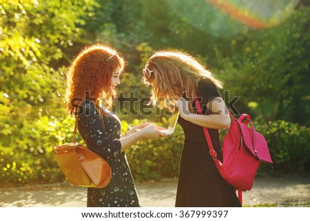 Young gay girlfriends in a city park. The girl is holding a notebook. My friend looks at laptop screen girlfriend. Social networking. Best friends. BFF - stock photo