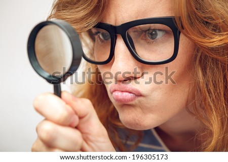 Young geek looking through magnifying glass. - stock photo