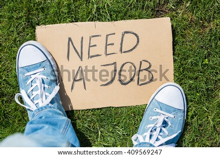 "Young generation employment concept: man with ""need a job"" cardboard - stock photo"