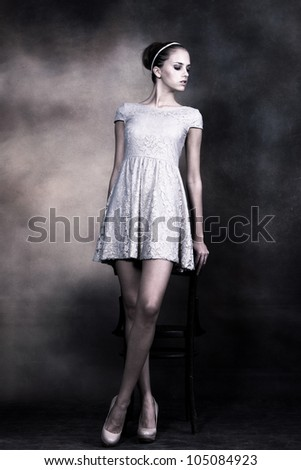 young gentle woman with bun styled hair in delicate lacy dress, full body shot, - stock photo