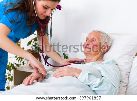 Young geriatrician doctor listening to the lung and hearth sounds of a senior patient. - stock photo