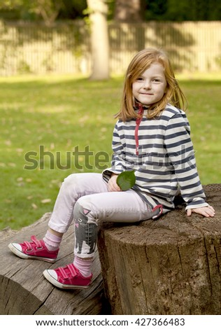 Young Girl. A five year old girl sits on a fallen tree trunk holding a green leaf and smiling at the camera. - stock photo