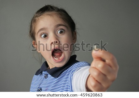 Young girl (age 6) surprise to find that she have lost her first bottom front milk teeth. Childhood healthcare concept. real people copy space - stock photo