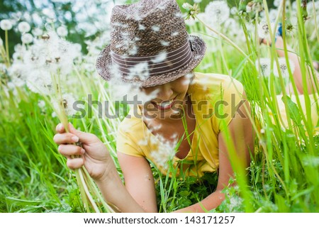 young girl among dandelions summer day - stock photo