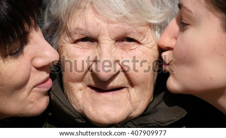 Young girl and adult woman kissing grandmother on cheeks, Granny smiling and looking to the camera. Three family generations. Grandmother, mother and granddaughter. - stock photo