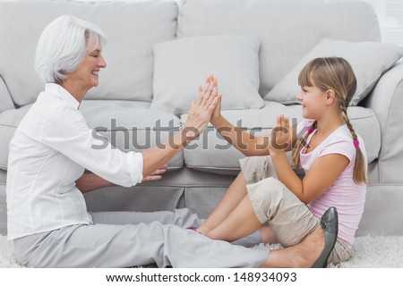 Young girl and grandmother playing together sat on a carpet in the living room - stock photo
