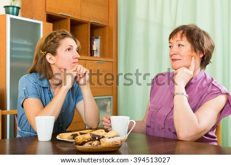 Young girl and her aged mother having tea-drinking at the table and talking - stock photo