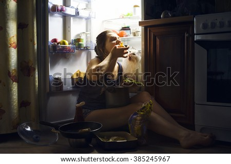 young girl and her fluffy cat eating at night - stock photo