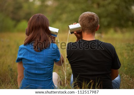 young girl and man playing with tin. outdoor shot - stock photo