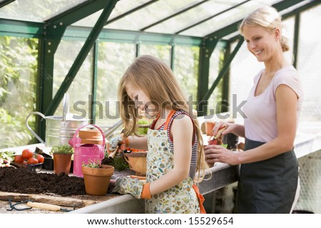 Young girl and woman in greenhouse putting soil in pots smiling - stock photo