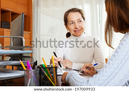 Young girl answering questions of with computer employee at office - stock photo