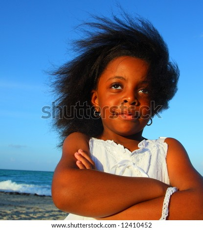 Young girl at the beach with arms crossed - stock photo