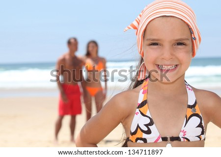 Young girl at the beach with her parents - stock photo
