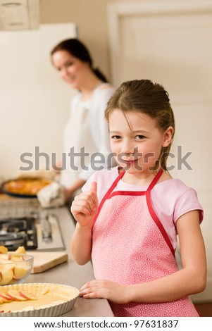 Young girl baking apple pie thumb up tasting with mother - stock photo