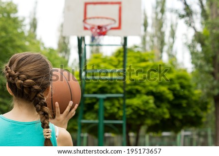 Young girl basketball player taking aim with the ball at the goal as she practices her game on an outdoor court - stock photo
