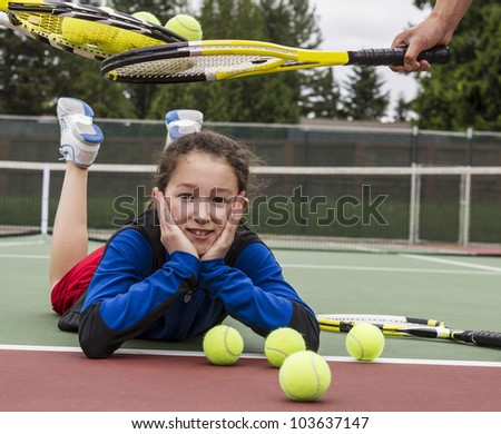 Young girl being given acceptance into tennis group with rackets over her head - stock photo