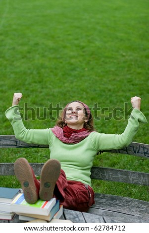Young girl being happy while reading some books in a park - stock photo