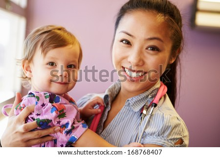 Young Girl Being Held By Female Pediatric Doctor - stock photo