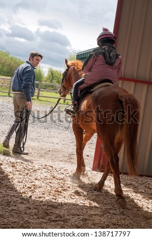 Young girl being lead out of the indoor arena - stock photo