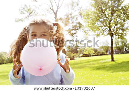 Young girl blowing a pink balloon in the park on a sunny day. - stock photo