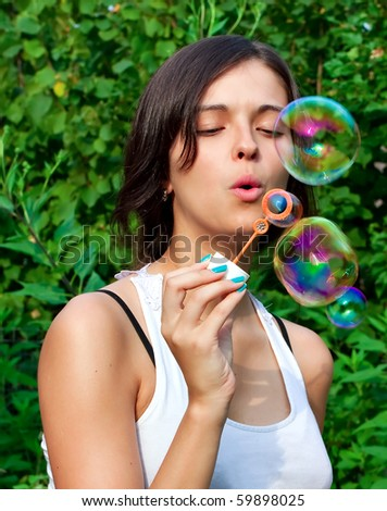 Young girl blowing soap bubbles in autumn park - stock photo