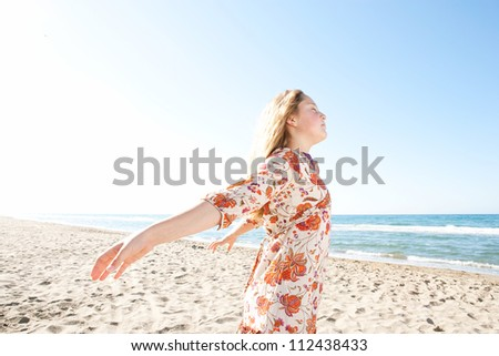 Young girl breathing fresh air while enjoying the sun on a golden sand beach with a blue sky and the sea horizon in the background. - stock photo
