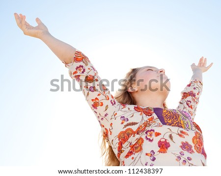 Young girl breathing fresh air with her arms raised  against a blue sky. - stock photo