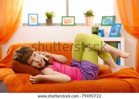 Young girl calling on mobile phone on living room sofa.? - stock photo