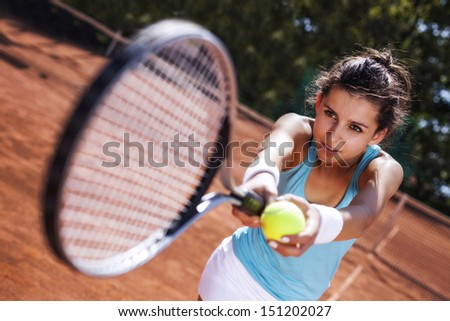 Young girl catching a ball in tennis court in pretty day - stock photo