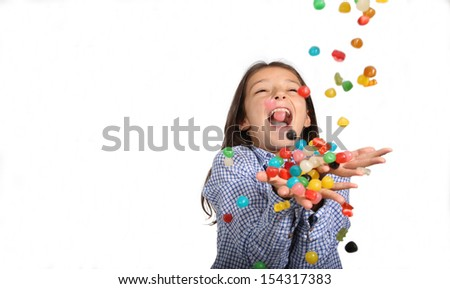 Young girl catching candies falling from the sky on a white background with copy space - stock photo