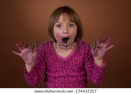 young girl caught eating blueberries with messy face. Part of a series - stock photo