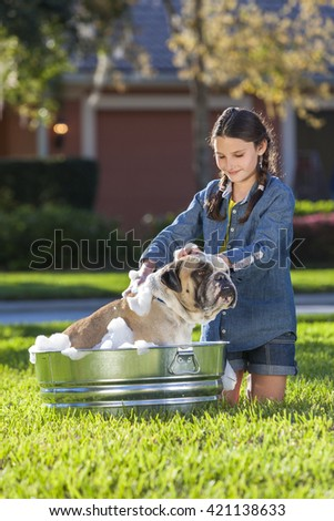 Young girl child washing her pet dog, a bulldog, outside in a metal tub - stock photo