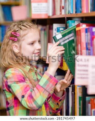 young girl chooses a book in the library - stock photo
