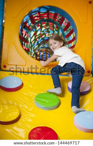 Young girl climbing up ramp into tunnel at soft play center - stock photo